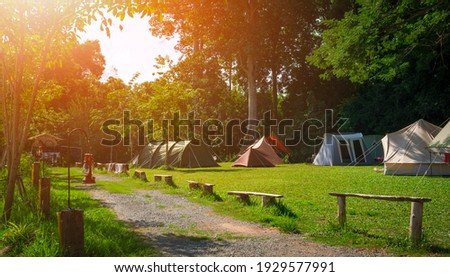 Morning sunlight on surface of various field tents group on green lawn in campsite area at natural parkland Stock photo ©