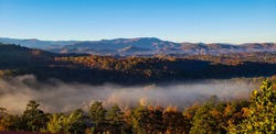 Morning sunshine and mist covering mountains full pf fall colors at Great smoky mountains.