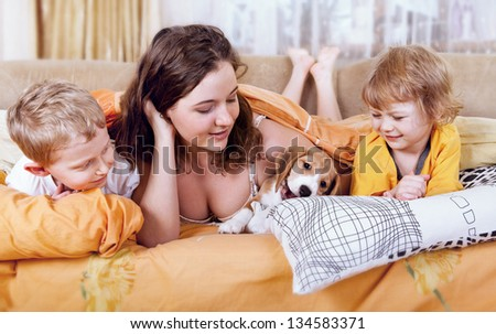 Morning time scene. Children  with beagle puppy in the bed