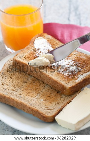 Morning toast with butter and a glass of fresh orange juice - stock photo