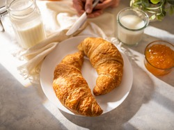 Morning traditional breakfast consisting of two croissants on a white plate, milk and orange jam. White napkin. High angle view. A restaurant. Cafe. Home kitchen. Delicious and healthy food.