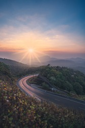 Morning view of curved road with sunrise and mountainous area. shallow depth of field.