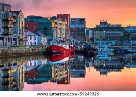 morning view on row of buildings and fishing boats in Galway Dock with sky reflected in the water, HDR image - stock photo