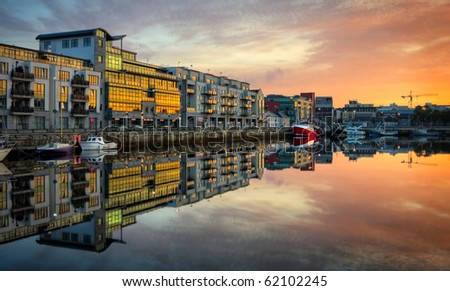 Stock Photo morning view on row of buildings and fishing boats in Galway Dock with sky reflected in the water, HDR image