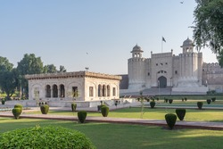 Morning view with garden and marble pavilion of white Alamgiri gate built by mughal emperor Aurangzeb as entrance to Lahore fort, a UNESCO World Heritage site, Punjab, Pakistan