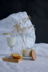 morning, white bed, on it is a glass of milk, glass on a leg, stands on a wooden stand, on it is a cookie cracker, a glass vase with dried flowers and a candle.