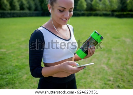 Shutterstock Morning workout. Portrait of young healthy athletic woman in sportswear choosing music set for jogging with mobile application in green summer park outdoors.