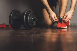 Morning workout routine in home gym. Fitness motivation and muscle training concept. Man in sneakers tying shoelaces. Athlete starting exercise with dubbell weight.