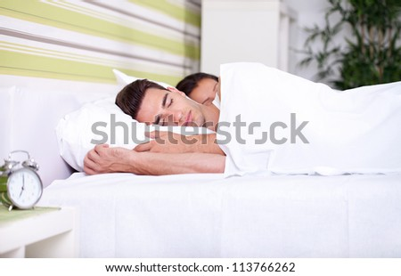Morning , young couple sleeping together in bed