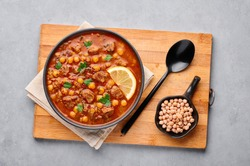 Moroccan Harira Soup in black bowl at grey concrete table top. Harira is Moroccan Cuisine dish with lamb or beef meat, chickpeas, lentils, tomatoes, ciliantro. Ramadan Iftar Food. Top view