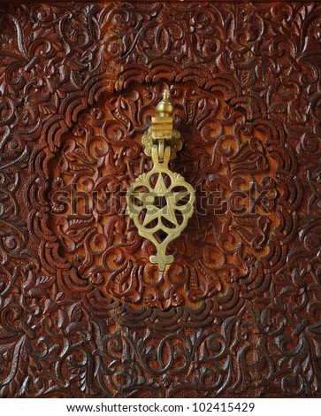 Moroccan style door knocker on an intricately carved wooden door