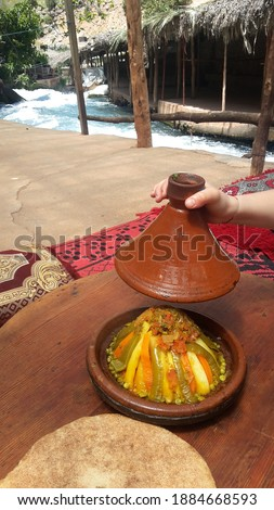 Moroccan vegetable tagine on a berber carpet at the edge of the Oum Rabie water source in the Middle Atlas Stock photo ©
