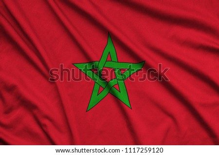 Morocco flag  is depicted on a sports cloth fabric with many folds. Sport team banner #1117259120