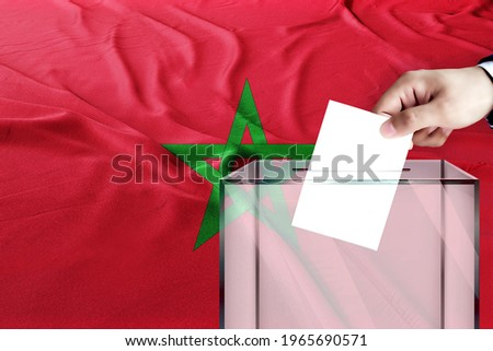 morocco flag, morocco  the symbol of elections Male hand puts down a white sheet of paper with a mark as a symbol of a ballot paper against the background
