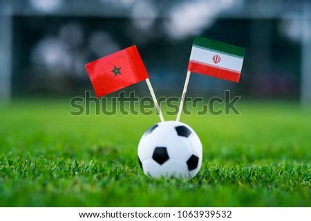 Morocco - IR Iran, Group B, Friday, 15. June, Football, National Flags on green grass, white football ball on ground. #1063939532