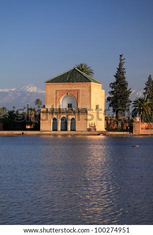 Morocco Marrakesh Menara Pavilion and Gardens reflected on lake in late afternoon sunshine with snow covered peaks of the Atlas Mountains in the background