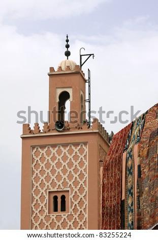 Morocco Marrakesh Minaret of small mosque in Djemma el Fna square - traditional Berber carpets on display next door