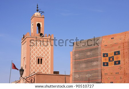 Morocco Marrakesh Mosque minaret and typical Berber rugs hanging in the sunshine in Jemaa El Fna Square