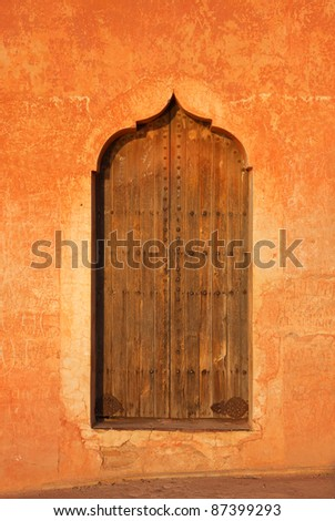 Morocco Marrakesh typical old arabesque door surrounded by rustic terracotta colored wall - Menara Pavilion