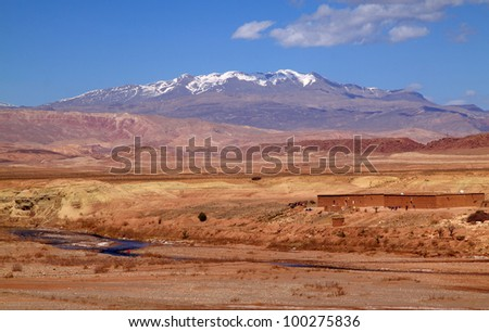 Morocco Ouarzazate -  panorama of the river valley between Ouarzazate and Ait Ben Haddou in the late afternoon sunshine with snow covered peaks of the Atlas Mountains in the background