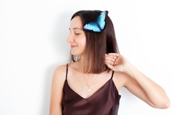 Morpho butterfly on the hair of a beautiful young brunette. White background, space for text. Beauty. Care. Nature. High quality photo
