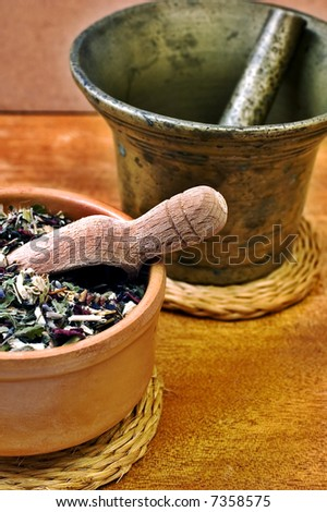Mortar and bowl with herbs with selective focus