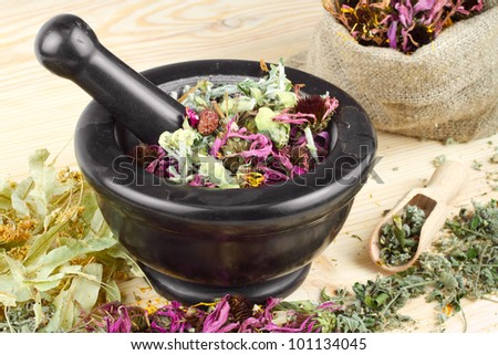 mortar and pestle and sack with healing herbs on wooden table