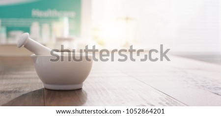 Mortar and pestle on the pharmacist's table and pharmaceutical products on the background #1052864201