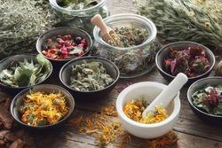 Mortar, bowls and jars of dry medicinal herbs on table. Healing herbs assortment. Alternative medicine.