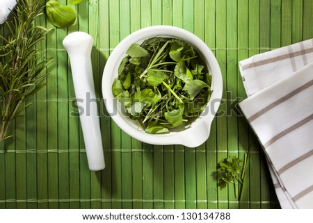 mortar filled with herbs and pestle on green bamboo mat