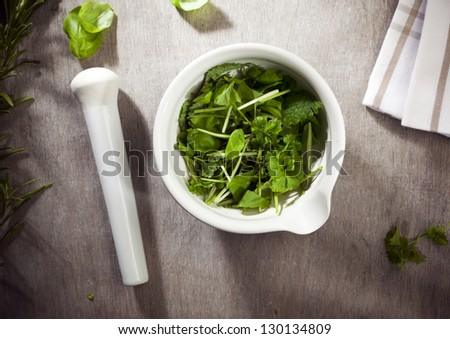 mortar filled with herbs and pestle on table