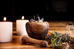 Mortar with dried healing herbs, flowers and candles, ritual purification and cleansing, copyspace