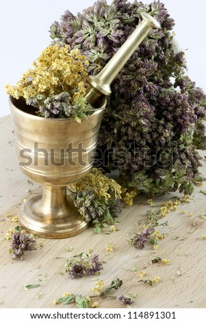 Mortar with dry herbs on the table. Focus on the front.
