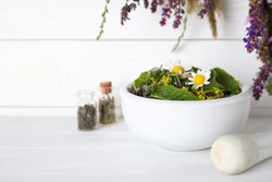 Mortar with healing herbs and pestle on white wooden table