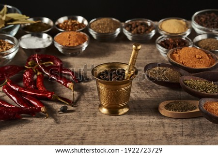 mortar with pepper peas on a background of bowls with spices dried red pepper and wooden spoons with spices on a wooden surface Stockfoto ©