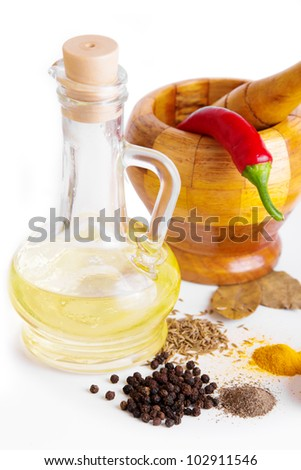 Mortar with pestle, variety of spices and oil over white