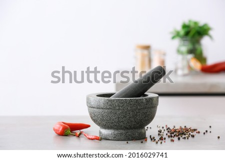 Mortar with spices and pestle on light table in kitchen Foto d'archivio ©