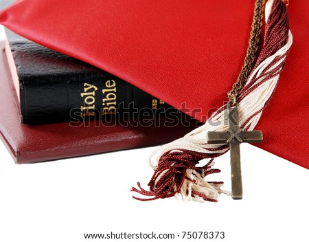 mortarboard with tassel, diploma, bible and cross - for a religious graduation theme, isolated on white - stock photo