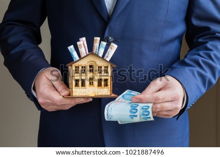 Mortgage and real estate investment.the man holds money and house.