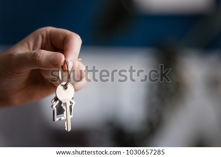 Mortgage concept. Men hand holding key with house shaped keychain. Modern light lobby interior. Real estate, moving home or renting property.