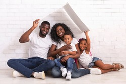 Mortgage For Young Families. Happy Black Parents And Their Two Kids Sitting Under Symbolic Roof Dreaming Of New Home Over White Wall Background