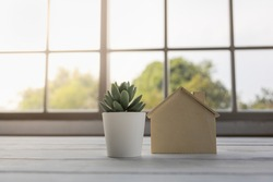 Mortgage, Home Loan Concept. Closeup of wooden mini house toy with green plant pot on wooden table.
