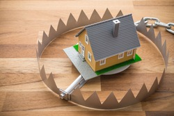 Mortgage house in a bear trap on wooden table background. House trap on debt or loan problem or risk in real estate property financing concept.