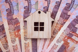 Mortgage, insurance, buying and rent, real estate business concept. Small wooden house toy on money rouble banknotes background top view