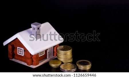 Mortgage loan and real estate tax macro financial Concept, Scandinavian house model and pile of coins money on dark black background. #1126659446