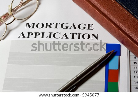 Mortgage loan application form and notebook macro - stock photo