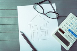 Mortgage or loan concept. A drawing of a house and calculator