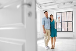 mortgage, people and real estate concept - happy couple hugging at new home