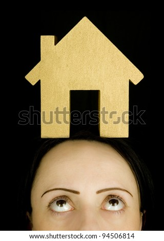 mortgage worry, woman looking up at gold house on her head