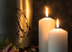 Mortuary urn with burning candles and flowers against dark background Churches and funeral concept. Copy space on left hand side. Funeral symbol. Mourn and Condolence card concept. End of life.